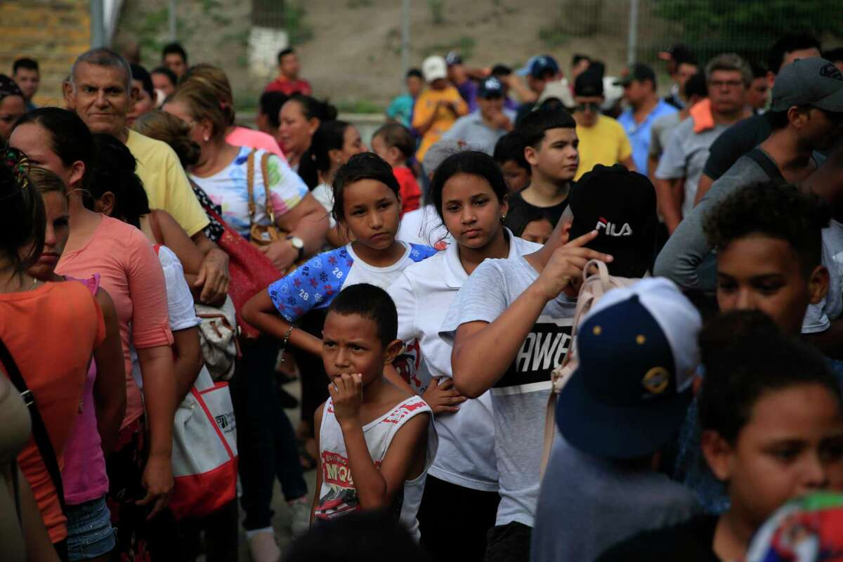 Migrants from countries including Honduras, Cuba, Venezuela, and Nicaragua, line up to receive a meal donated by volunteers from the U.S., at the foot of the bridge that crosses to Brownsville, Texas, in downtown Matamoros, Tamaulipas state, Mexico, Wednesday, June 26, 2019. Hundreds of migrants, some of whom have been in line for months, are awaiting their turn to request asylum in the U.S.