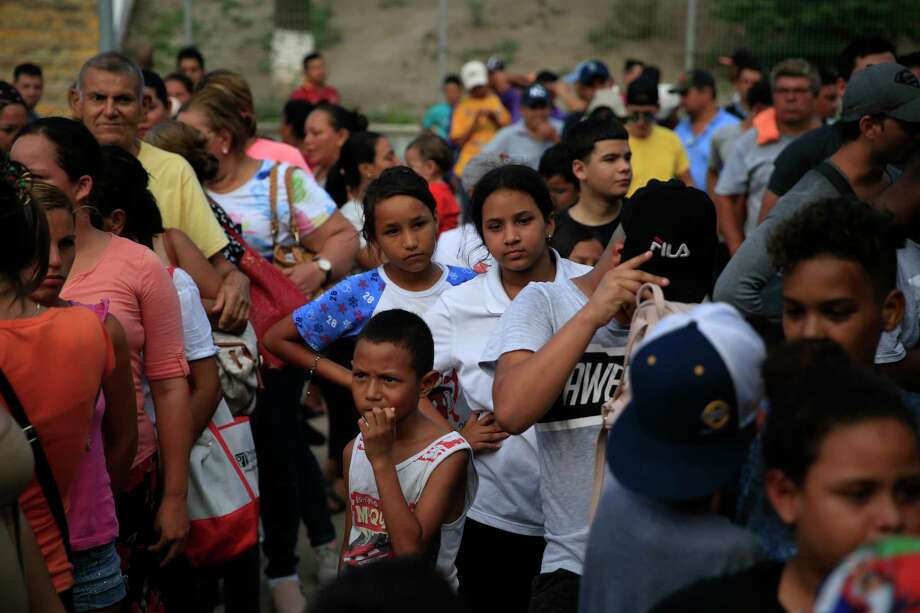 Migrants from countries including Honduras, Cuba, Venezuela, and Nicaragua, line up to receive a meal donated by volunteers from the U.S., at the foot of the bridge that crosses to Brownsville, Texas, in downtown Matamoros, Tamaulipas state, Mexico, Wednesday, June 26, 2019. Hundreds of migrants, some of whom have been in line for months, are awaiting their turn to request asylum in the U.S. Photo: Rebecca Blackwell, AP / Copyright 2019 The Associated Press. All rights reserved.