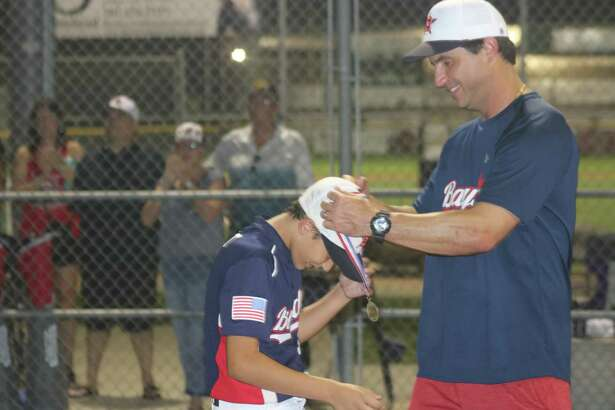 Shane Helmle presents another medal to one of his players during postgame ceremonies Wednesday night. The ceremonies also included a district championship flag for the boys.