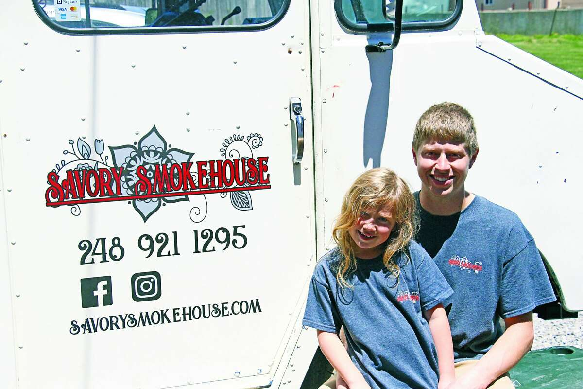 Savory Smokehouse Owner Forrest Maxwell and his daughter, Penelope, sit in front of the business's food truck.