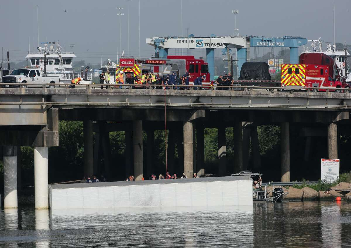 The Harris County Sheriff's Office investigates the scene where an 18-wheeler crashed off Interstate 10 westbound and into the San Jacinto River Thursday, June 27, 2019, in Channelview, Texas.