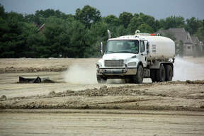 A truck dampens the soil to keep the dust down Wednesday in a back section of Plummer Family Park in Edwardsville.