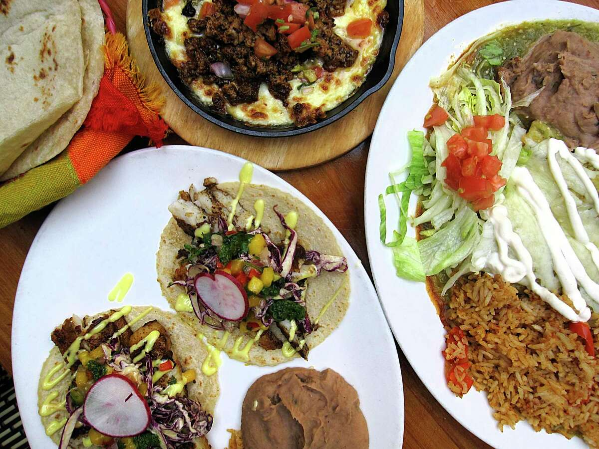 Dishes include, clockwise from top, queso fundido with chorizo and handmade tortillas, enchiladas verde with chicken and fish tacos at CoCo Bongo Cocina & Bar.