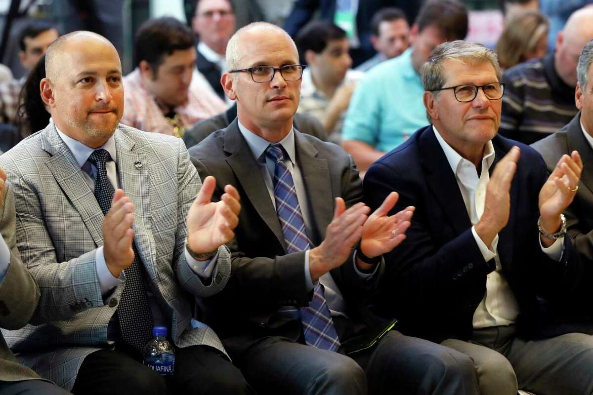 UConn Director of Athletics David Benedict, left, men's basketball coach Dan Hurley, center, and women's basketball coach Geno Auriemma applaud during the announcement that UConn would be re-joining the Big East Conference last June at Madison Square Garden.