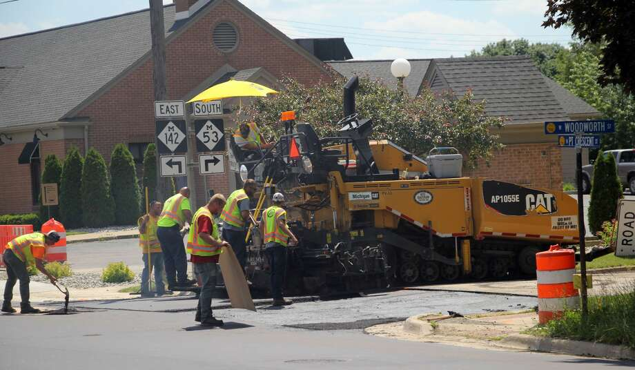 Crews worked diligently Thursday to pour the final layers of asphalt onto North Port Crescent Street, near West Woodworth Street. Phase II road construction replaced all the infrastructure under North Port Crescent, including the storm drain and water and sewer lines. The road is expected to reopen sometime today. Photo: Seth Stapleton/Huron Daily Tribune