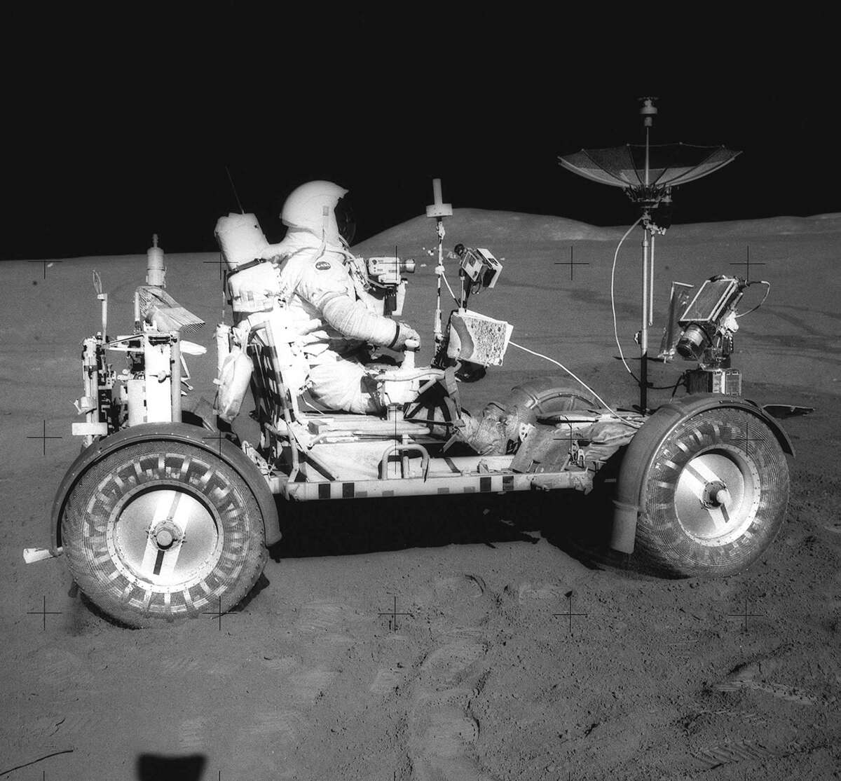 This 1971 photograph was taken during the Apollo 15 mission on the lunar surface. Astronaut David R. Scott waits in the Lunar Roving Vehicle (LRV) for astronaut James Irwin for the return trip to the Lunar Module, Falcon, with rocks and soil collected near the Hadley-Apernine landing site.