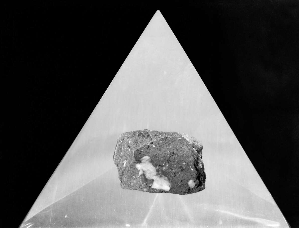 This Apollo 16 lunar sample (moon rock) was collected by astronaut John W. Young, commander of the mission, about 15 meters southwest of the landing site. The rock, shown here in a 1972 photo, weighed 128 grams when returned to Earth. The sample is a polymict breccia. This rock, like all lunar highland breccias, is very old, about 3,900,000,000 years older than 99.99% of all Earth surface rocks, according to scientists.