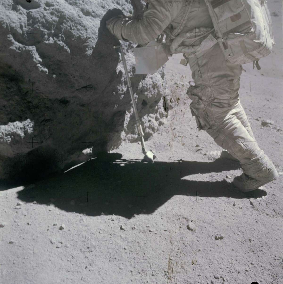 """Astronaut Charles M. Duke Jr., lunar module pilot, works at the """"Shadow Rock"""", discovered during the missions third extravehicular activity (EVA) in the area of North Ray Crater (Station 13) on April 23, 1972. The scoop, a geological hand tool, leans against the rock. This view was exposed by astronaut John W. Young, commander. The two moon-exploring crew men sampled this rock, which got its name because of a permanently shadowed area it protected."""