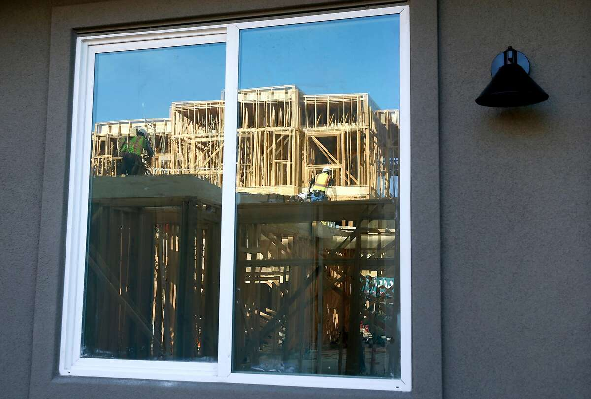Framework of a residential building under construction is reflected on the window of a unit nearing completion at the Ice House development by City Ventures in Oakland, Calif. on Thursday, June 27, 2019.