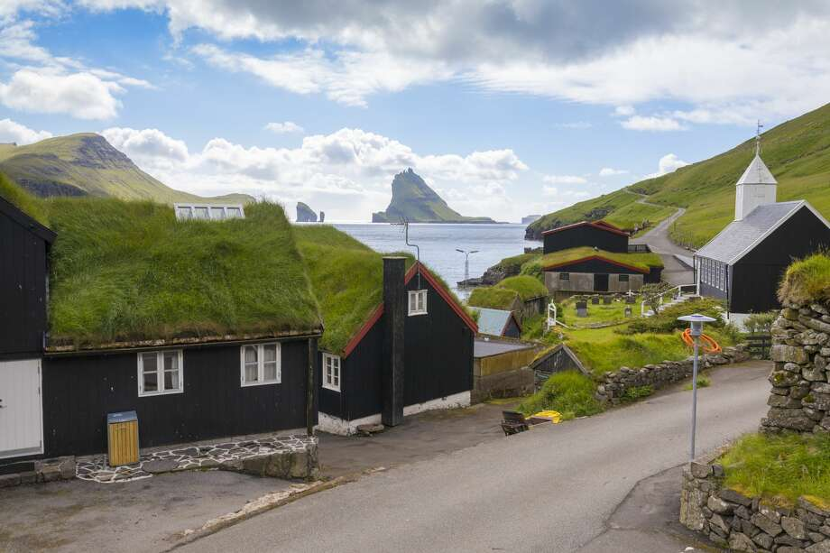 Love a view? You'll be obsessed with the Faroe Islands. Here is the village of Bøur, with incredible views of the seastacks of Drangarnir and islet of Tindhólmur. Photo: Roberto Moiola/Getty Images/Robert Harding Worl