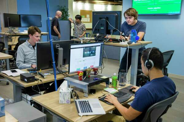 Pat Marion (left), Vadim Korolik (standing desk) and Julian Lin (right) work on the software at drive.ai on Wednesday, Aug. 9, 2017, in Mountain View, Calif. Drive.ai is a Silicon Valley startup that's creating artificial intelligence software for autonomous vehicles.