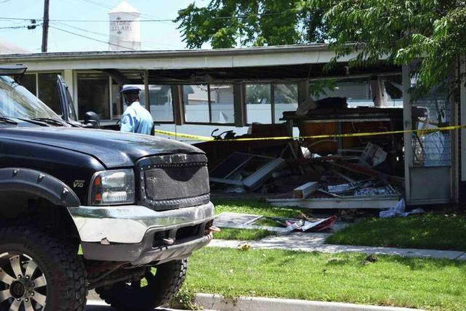 An Edwardsville police officer finishes taping off a scene where a black Ford F350 apparently crashed into an Edwardsville home. Photo: Tyler Pletsch | The Intelligencer