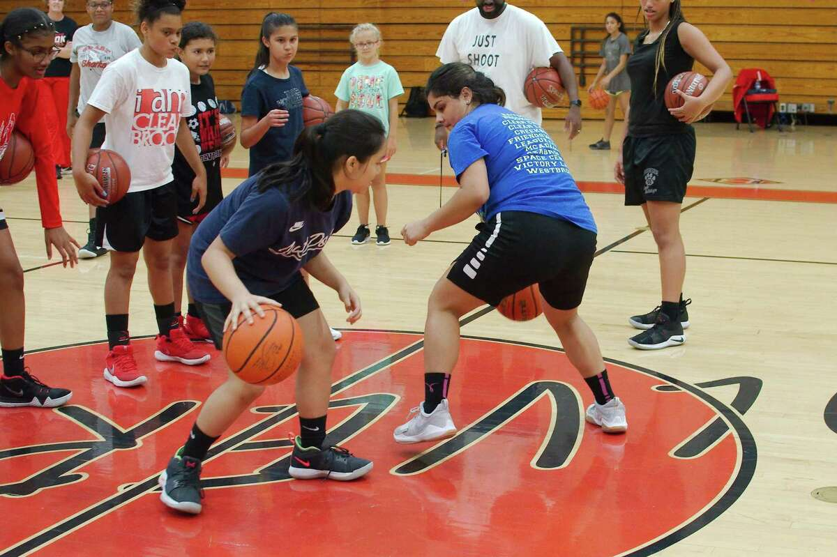 Katie Nguyen (left) and Raina Cantu participate in a ball handling competition at the Clear Brook summer basketball camp.