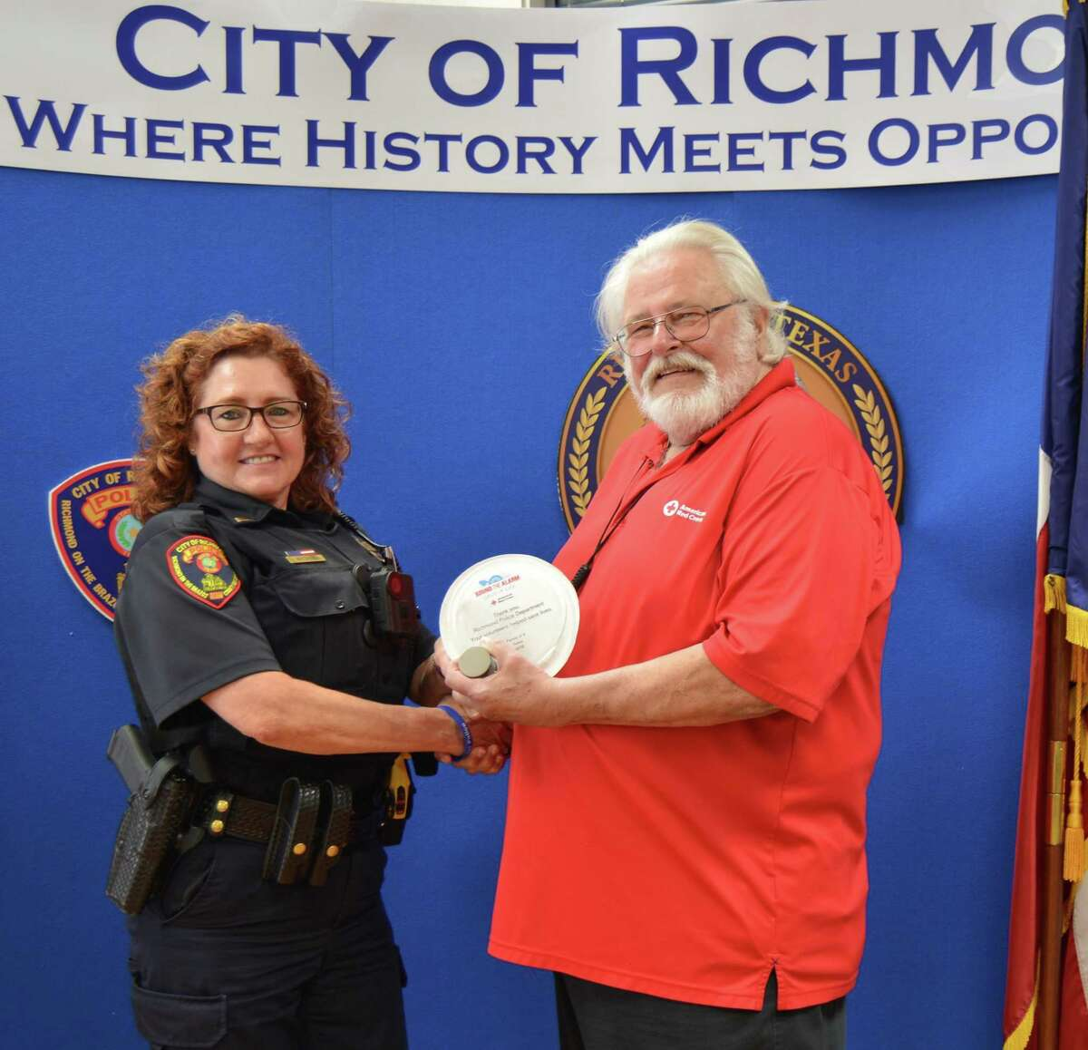 Lt. Diana Butinski of the Richmond Police Department receives the Partner Life Saving Award from Dave Spilman of the American Red Cross.