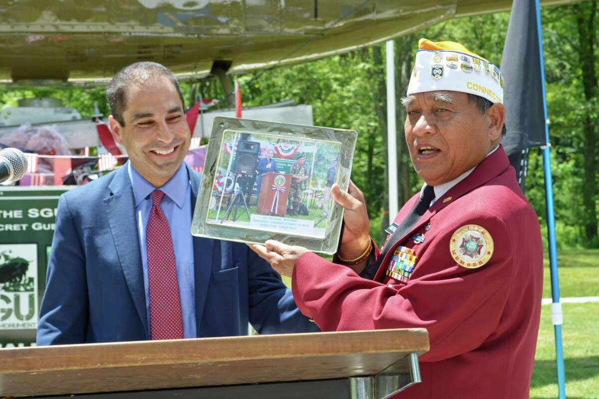 Hmong Gen. Sar Phouthasack presents a photograph to state Department of Veterans Affairs Commissioner Thomas Saadi. It shows them both at the dedication of the SGU National Monument in October 2018. Lt. Gov. Susan Bysiewicz joined veteran leaders at the Middletown Military Museum Thursday to sign a policy giving burial rights for the Hmong and Laotian Special Guerrilla Unit veterans in Connecticut who operated in support of the U.S. military during the war in Vietnam.
