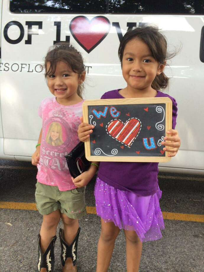 Lunches of Love kiddos, Miranda and Angel Sanchez, are happy to receive their nutritious meals. The Sugar Plum Market 2018 grant enabled Lunches of Love to pack and serve 24,000 lunches. Photo: Fort Bend Junior Service League / Fort Bend Junior Service League