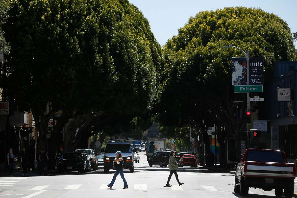 Pedestrians cross 24th Street, behind them trees along 24th Street can be seen, on Tuesday, June 25, 2019 in San Francisco, Calif.