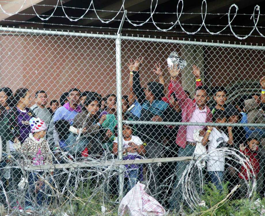 """FILE - In this March 27, 2019, file photo, Central American migrants wait for food in a pen erected by U.S. Customs and Border Protection to process a surge of migrant families and unaccompanied minors in El Paso, Texas. Texas Gov. Greg Abbott says he's sending another 1,000 National Guard troops to the U.S.-Mexico border and blasted Congress as a """"group of reprobates"""" over the growing humanitarian crisis. Abbott said Friday, June 21, 2019, that the additional Guard members will assist at detention facilities and at ports of entry. . (AP Photo/Cedar Attanasio, File) Photo: Cedar Attanasio, STF / Associated Press / Copyright 2019 The Associated Press. All rights reserved."""