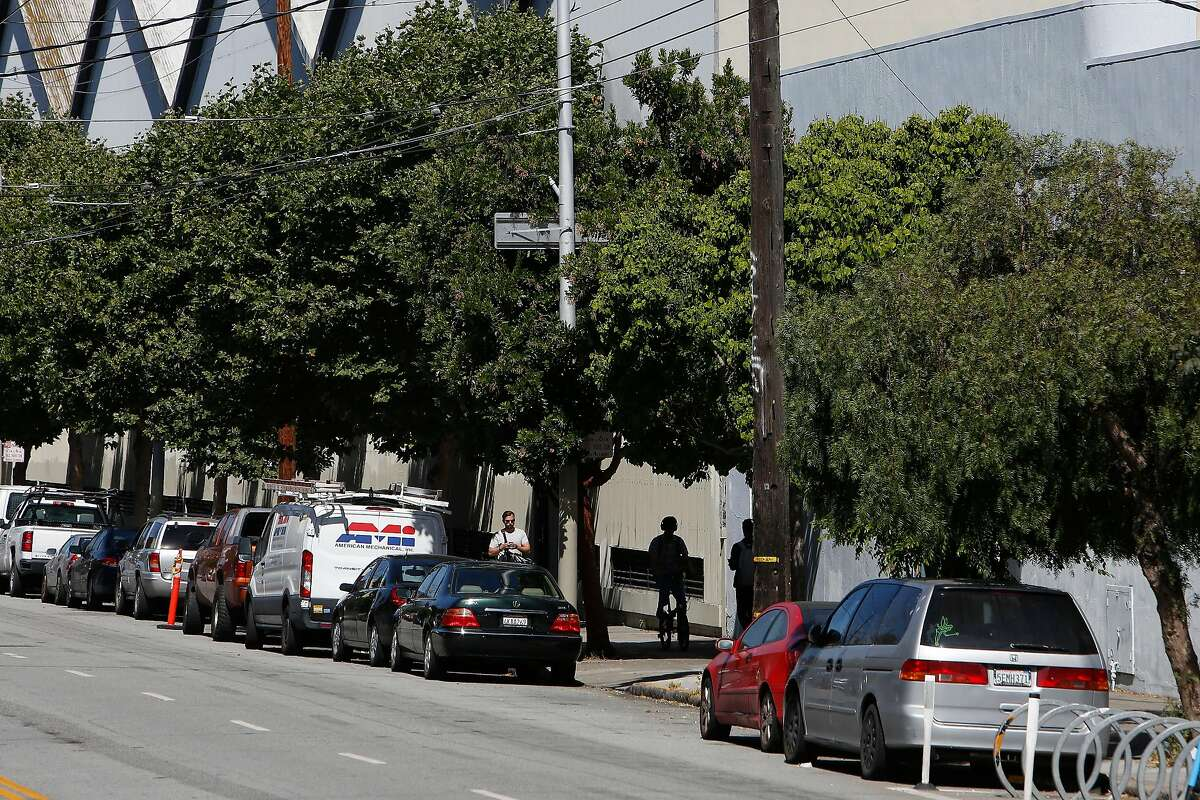 Pedestrians walk under trees along 16th Street between Harrison and Folsom Streets on Tuesday, June 25, 2019 in San Francisco, Calif.