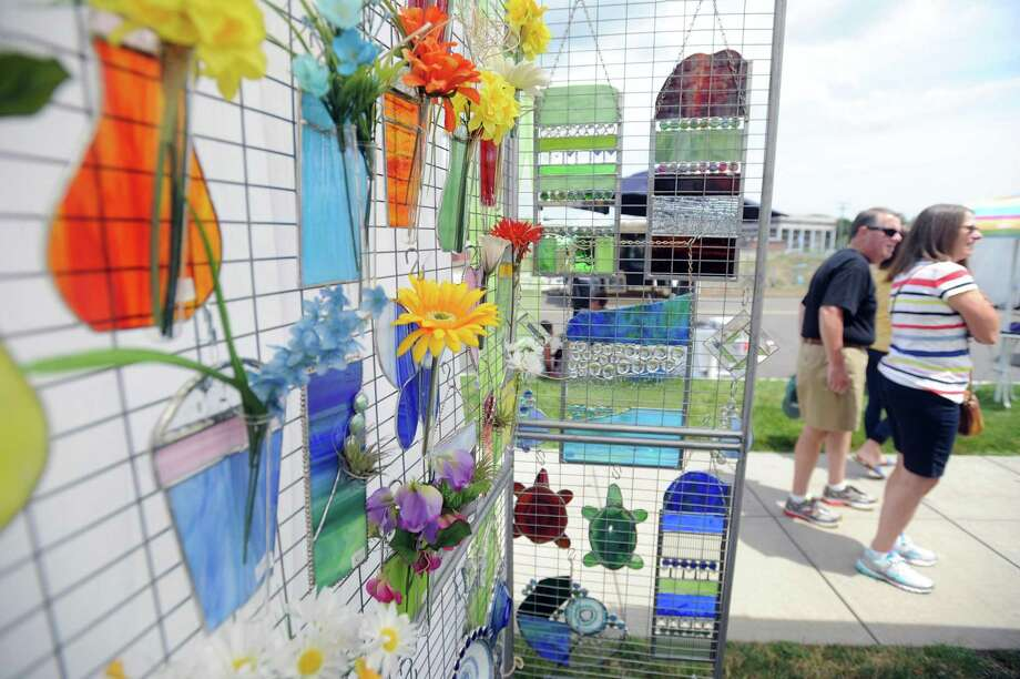 Visitors walk past stained glass art by Jennifer Webb, of Stamford, during last year's annual Stamford Art Festival, which takes place in the Harbor Point area. The event returns July 27 and 28. Photo: Hearst Connecticut Media File Photo / Stamford Advocate