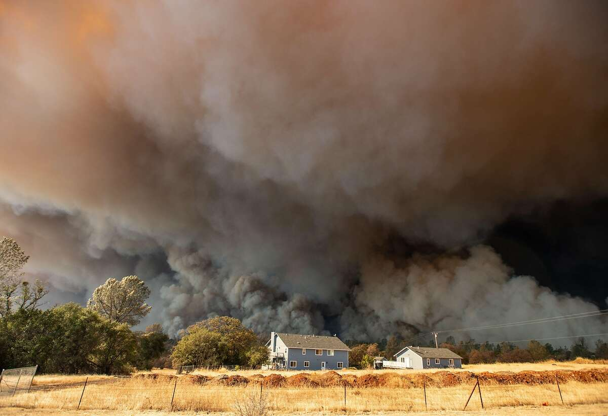 (FILES) In this file photo taken on November 8, 2018 a home is overshadowed by towering smoke plumes as the Camp Fire races through town in Paradise.
