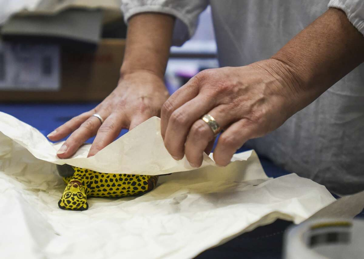 Elizabeth French wraps a yellow jaguar from John Gaston Fairey's collection of Mexican folk art after someone purchased it during the In the Eye of the Beholder event at the Art Museum of Southeast Texas Thursday evening. Photo taken on Tuesday, 6/27/19. Ryan Welch/The Enterprise