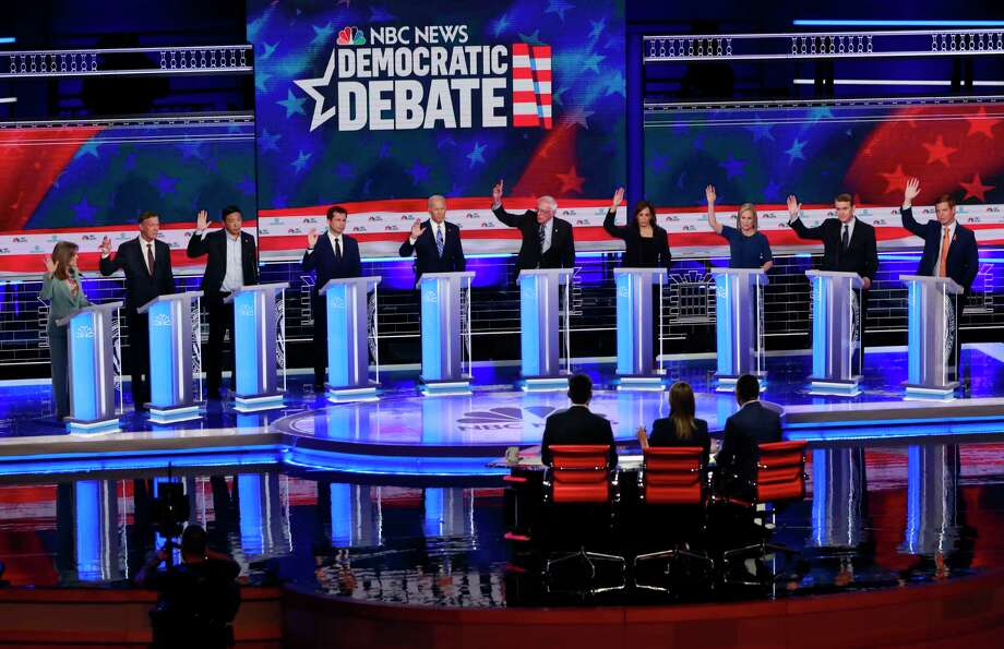Democratic presidential candidates, author Marianne Williamson, former Colorado Gov. John Hickenlooper, entrepreneur Andrew Yang, South Bend Mayor Pete Buttigieg, former Vice President Joe Biden, Sen. Bernie Sanders, I-Vt., Sen. Kamala Harris, D-Calif., Sen. Kirsten Gillibrand, D-N.Y., former Colorado Sen. Michael Bennet, and Rep. Eric Swalwell, D-Calif., raise their hands when asked if they would provide healthcare for undocumented immigrants, during the Democratic primary debate hosted by NBC News at the Adrienne Arsht Center for the Performing Arts, Thursday, June 27, 2019, in Miami. Photo: Wilfredo Lee, AP / Copyright 2019 The Associated Press. All rights reserved.