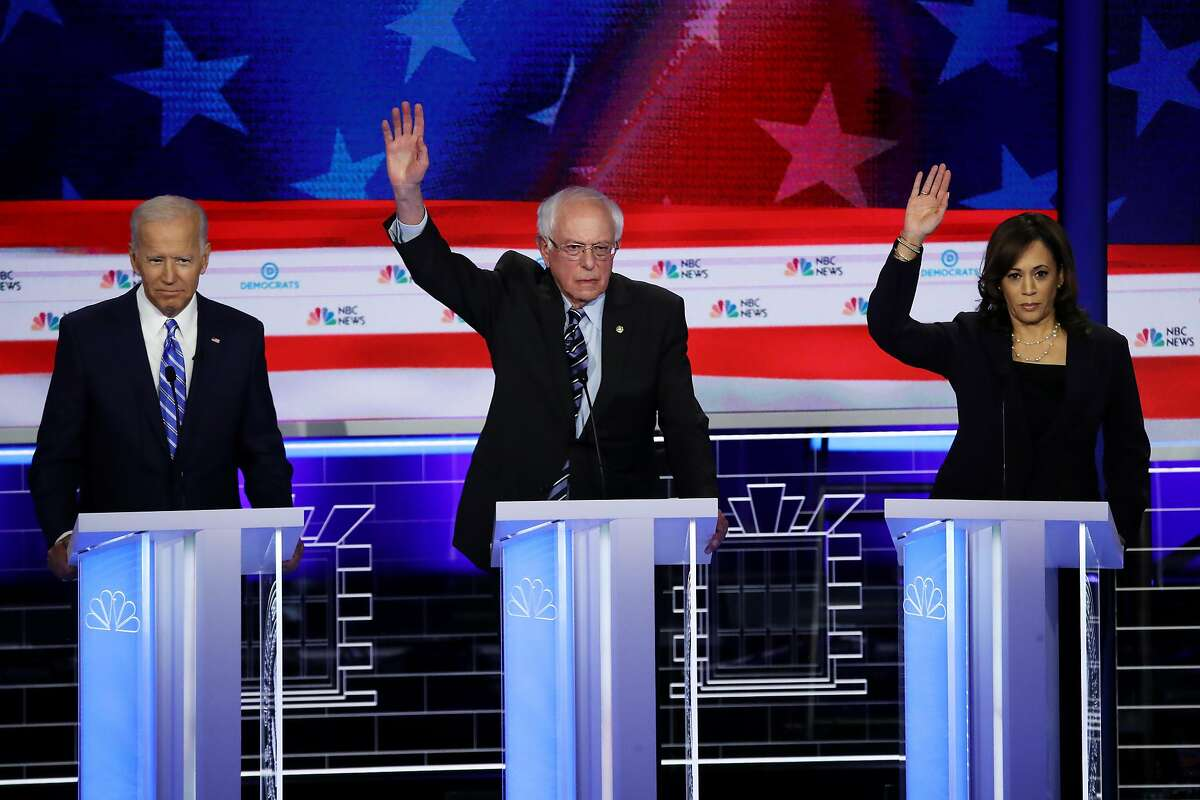 MIAMI, FLORIDA - JUNE 27: Former Vice President Joe Biden looks on as Sen. Bernie Sanders (I-VT) and Sen. Kamala Harris (D-CA) raise their hands during the second night of the first Democratic presidential debate on June 27, 2019 in Miami, Florida. A field of 20 Democratic presidential candidates was split into two groups of 10 for the first debate of the 2020 election, taking place over two nights at Knight Concert Hall of the Adrienne Arsht Center for the Performing Arts of Miami-Dade County, hosted by NBC News, MSNBC, and Telemundo. (Photo by Drew Angerer/Getty Images)