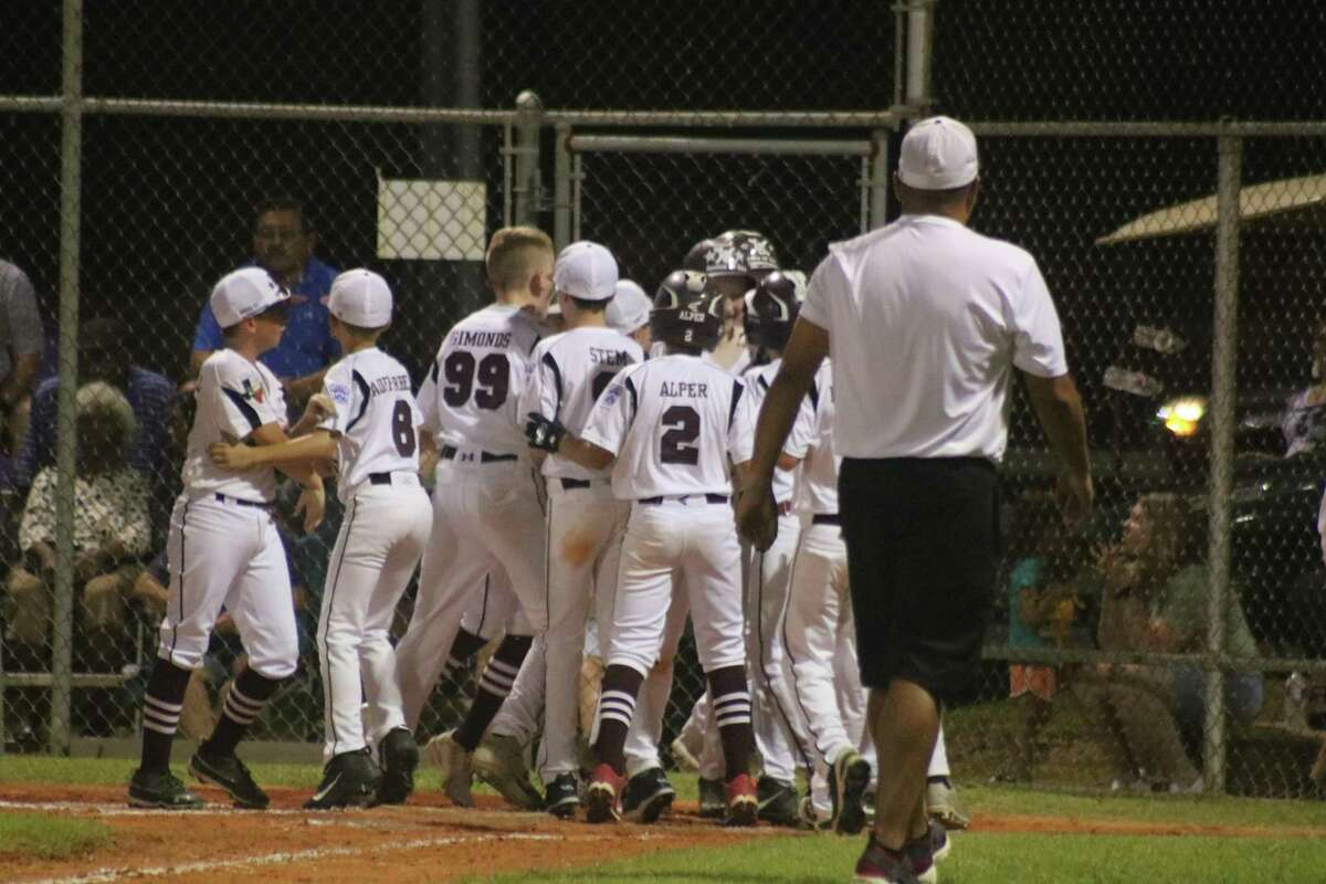 League City American players mob Connor Duhon after he connected for a three-run homer, giving his teammates a 4-0 lead. But the team couldn't protect it, losing in eight innings.