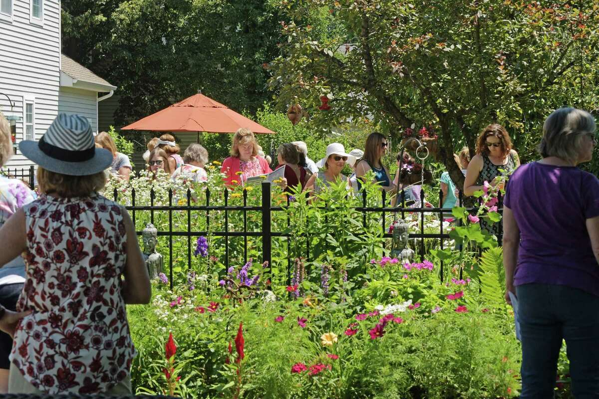 Visitors look at a garden in 2018 on the Secret Gardens Tour. The yearly event is presented by Soroptimist of Saratoga County and is a major fund-raiser to support local and global initiatives that benefit women, girls and the community. After being canceled last year due to COVID, the event is happening July 11 this year.(Paul Buckowski/Times Union)