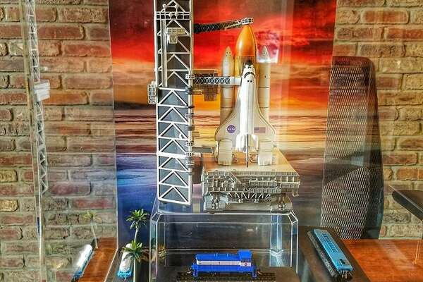 A NASA space shuttle replica surrounded by miniature train cars is on display at the Tomball Railroad Depot Museum as part of an exhibit to honor the 50th anniversary of the Apollo 11 moon landing.