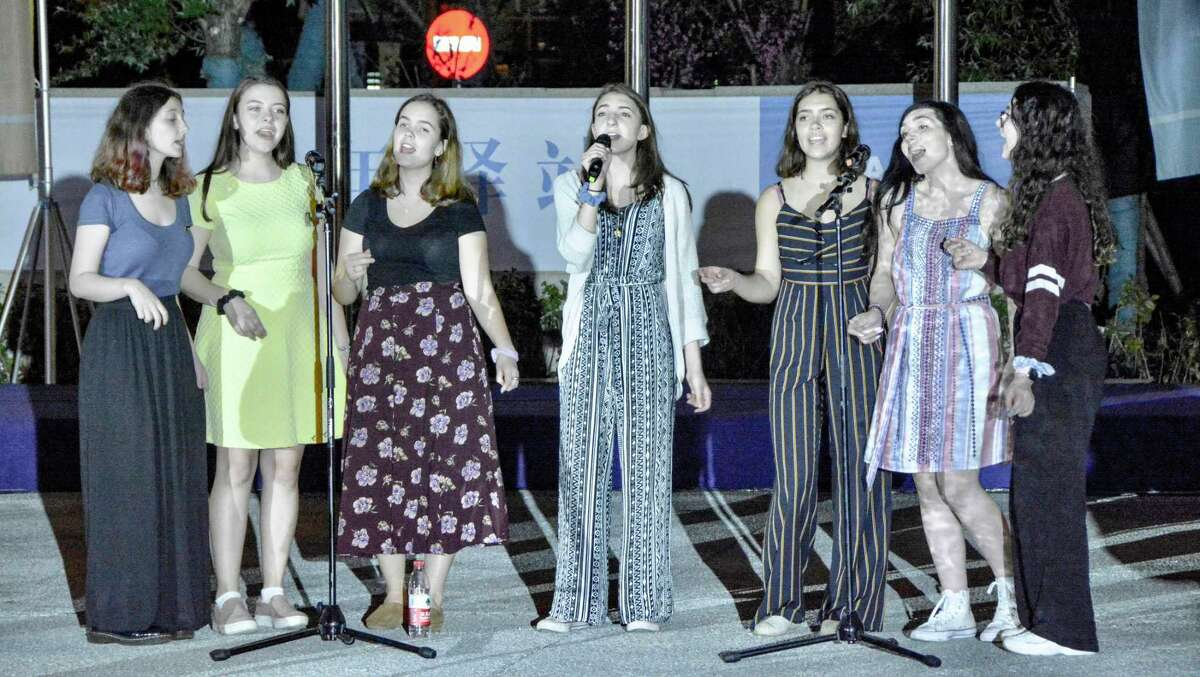 East Haven High School sophomore Alexis Ferreira (with microphone), who studies piano and singing at New Haven's ACES ECA, recently performing an a cappella set at an ACES-ECA partner school in Beijing.