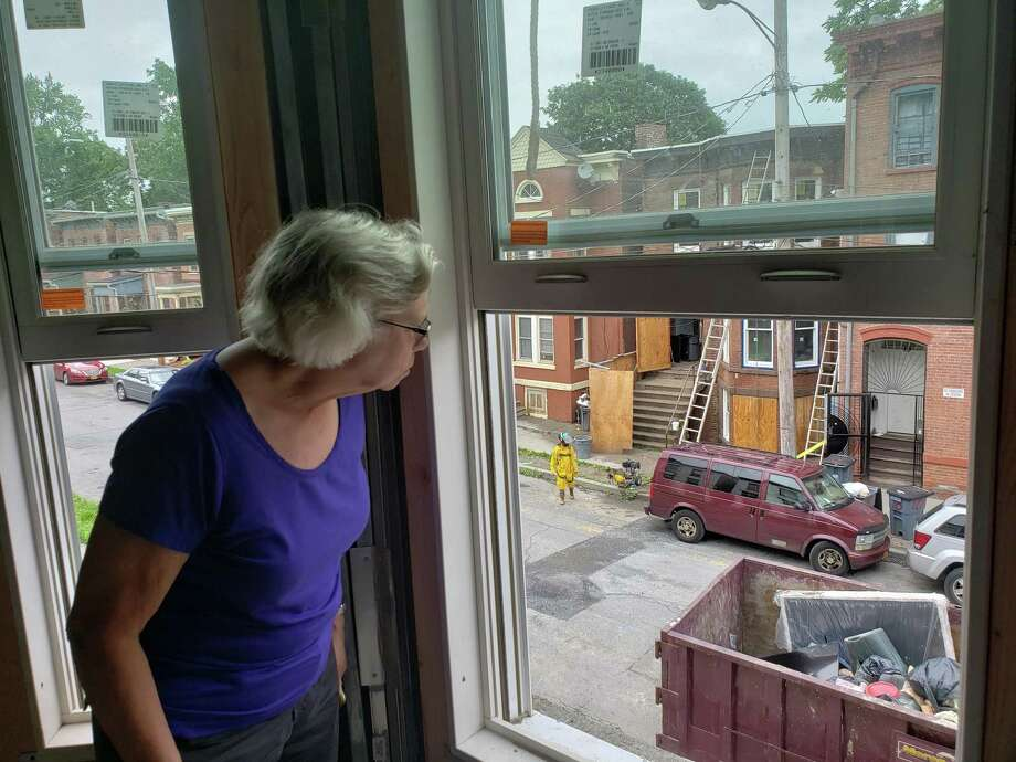 Lisa Daily, chair of the Newburgh Community Land Bank Board of Directors, looks out the window of a South Miller Street building under renovation at another building under renovation in Newburgh, N.Y. The buildings had been derelict before the land bank managed to find a developer. Photo: Michael Puffer / Republican-American / Republican-American; Contributed