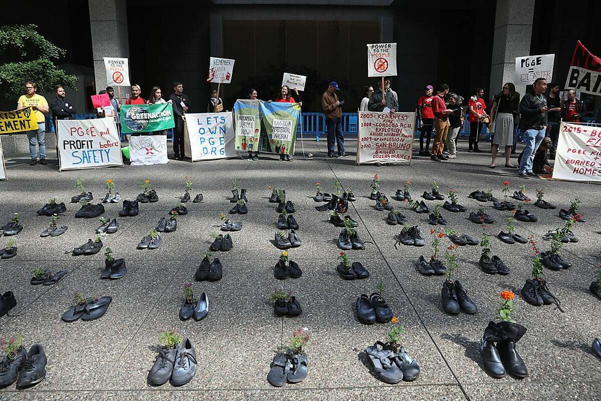 Democratic socialist groups laid down 85 pairs of shoes, one for each victim of he Camp Fire in front of PG&E headquarters on Friday, June 21, 2019 in San Francisco, Calif.