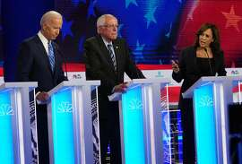 Former Vice President Joe Biden, left, looks down and grips his lectern as Sen. Kamala Harris (D-Calif.) speaks about her personal experience and his opposition to school busing in the 1970s during the Democratic presidential debate in Miami on Thursday night, June 27, 2019. At center is Sen. Bernie Sanders (I-Vt.). (Doug Mills/The New York Times)