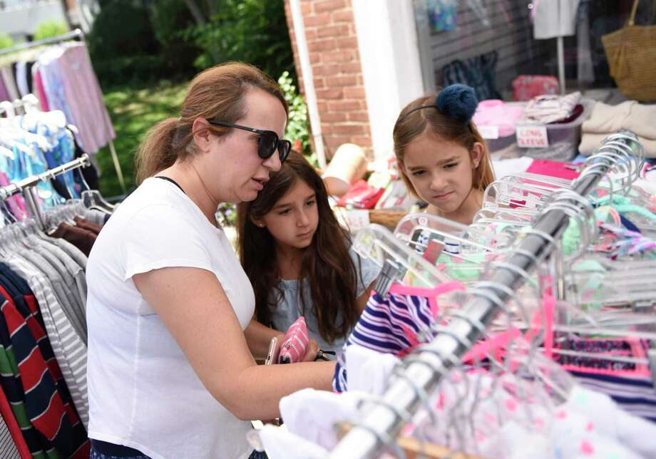 Old Greenwich's Jennifer Kutai shops with her kids Ellie and Hannah, 8, at Sound Beach Sportswear during the Old Greenwich Sidewalk Sales in Old Greenwich, Conn. Thursday, June 27, 2019. Presented by the Old Greenwich Merchants, several stores set out items at a bargain to attract shoppers. Photo: Tyler Sizemore / Hearst Connecticut Media / Greenwich Time