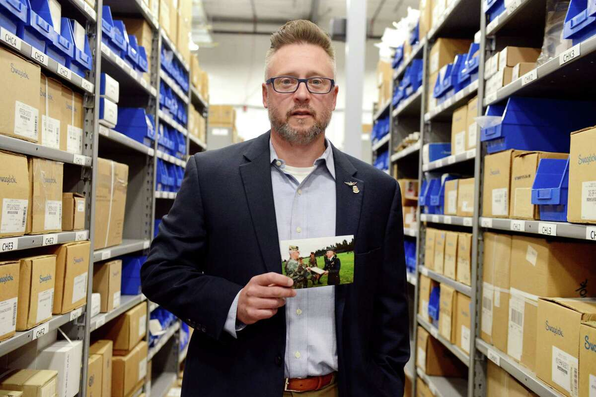 Veteran Michael Audette, salesperson at Swagelok Valve & Fitting Co., poses for a portrait in the companyOs warehouse with a picture of his graduation from college on Thursday, June 13, 2019 at Swagelok Valve & Fitting Co. in Clifton Park, N.Y. Audette used the GI Bill twice, both the Montgomery and Post-9/11 versions, to pay for college.(Catherine Rafferty/Times Union)