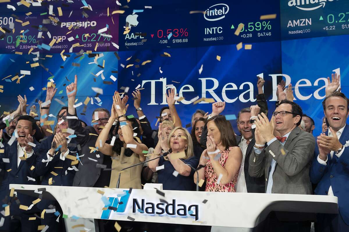 Julie Wainwright, center, CEO of The RealReal, celebrates her company's IPO at the Nasdaq opening bell, Friday, June 28, 2019 in New York. The online reseller of luxury brand clothing and accessories is based in San Francisco. (AP Photo/Mark Lennihan)
