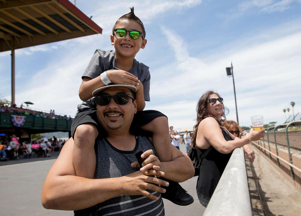 Michael Guzman of Union City cheers as his son, Anthony, 7, sits on his shoulders during the first horse race of the day held at the Alameda County Fairgrounds in Pleasanton, Calif. Thursday, June 27, 2019.
