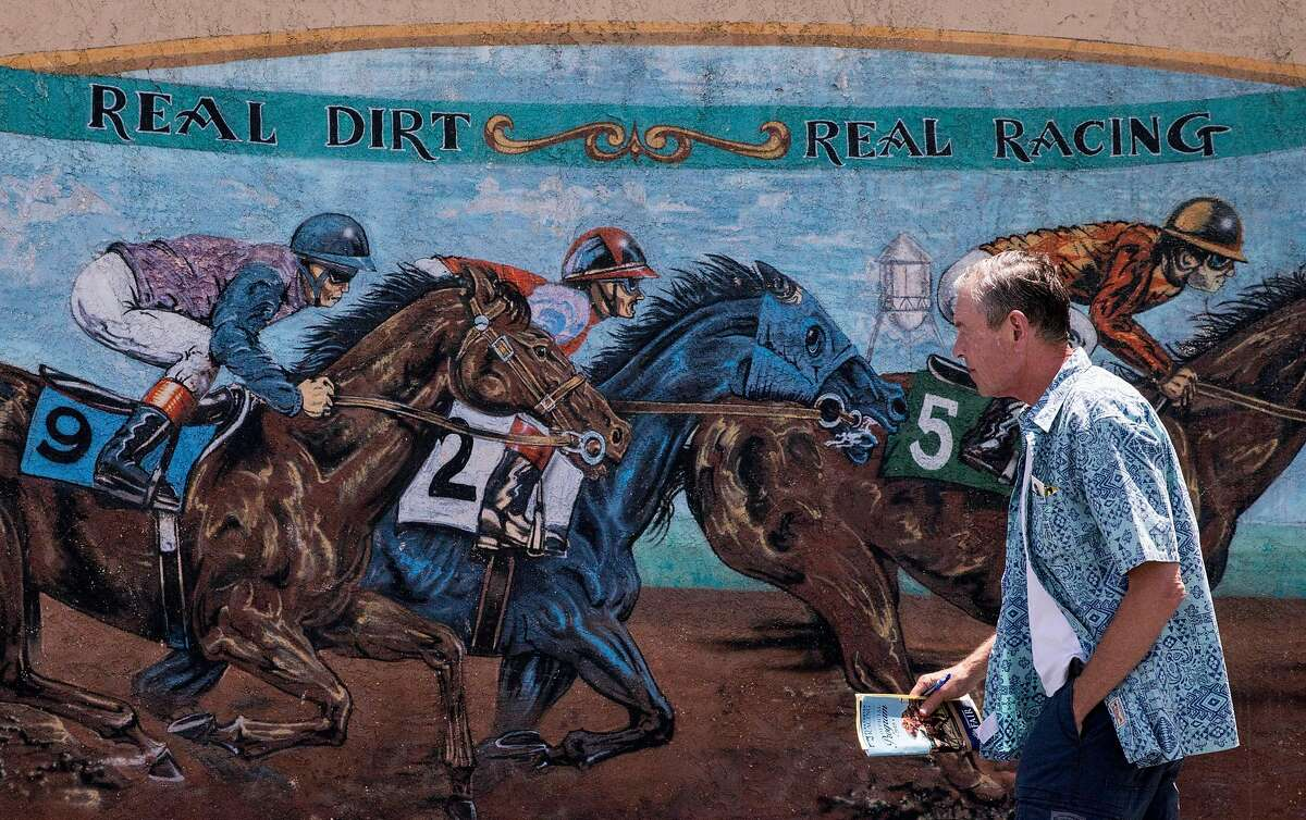 A racing fan walks past a mural painted on the side of the grandstands before the start of the horse races held at the Alameda County Fairgrounds in Pleasanton, Calif. Thursday, June 27, 2019.