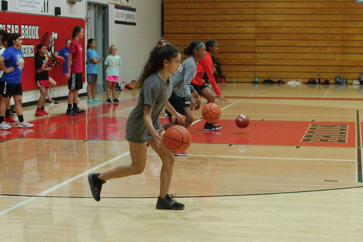 Alexia Velasquez, Kailyn Hitch and Kennedy Thompson participate in a dribbling drill at teh Clear Brook summer basketball camp.