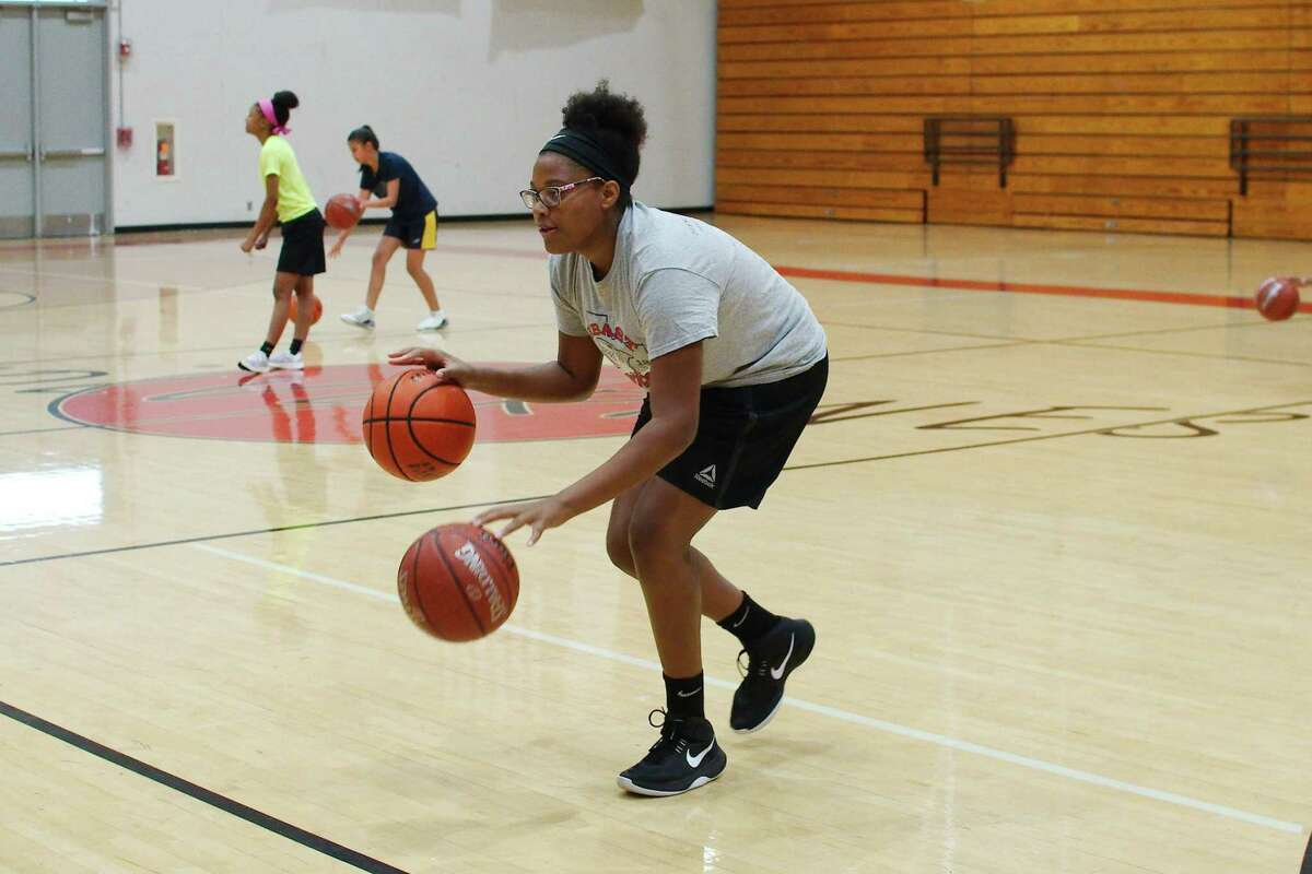 Lanae Montoute participates in a ball handling drill at the Clear Brook summer basketball camp.