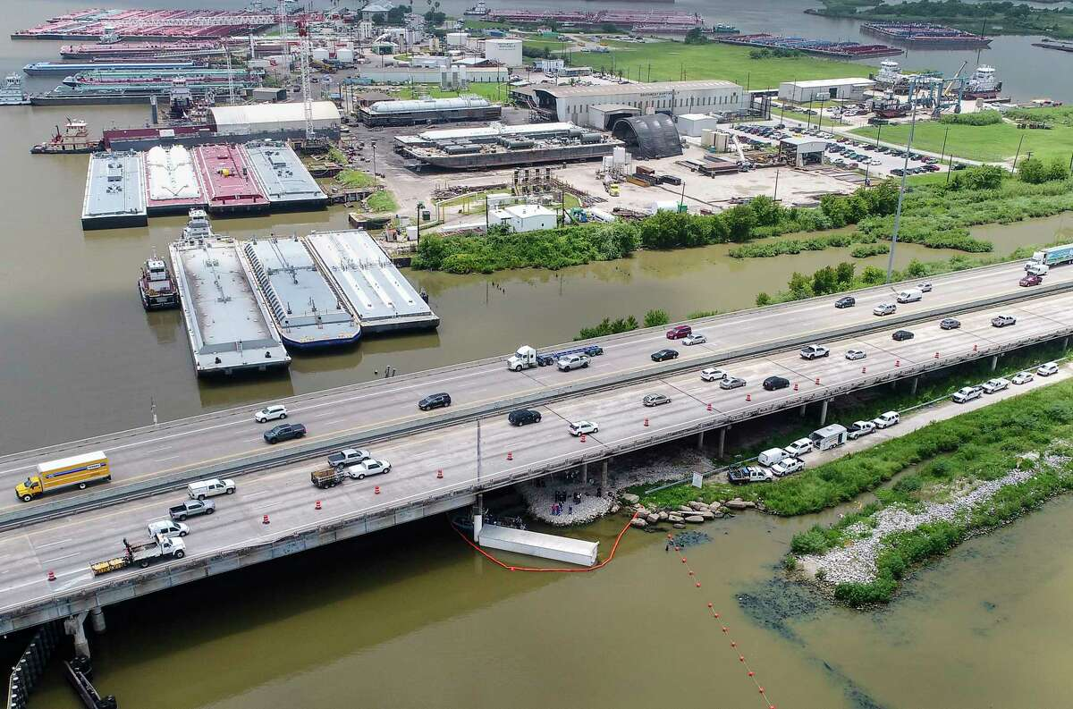 Authorities search for the missing driver of an 18-wheeler truck where it crashed off Interstate 10 westbound and into the San Jacinto River Thursday morning, on Friday, June 28, 2019, in Channelview.