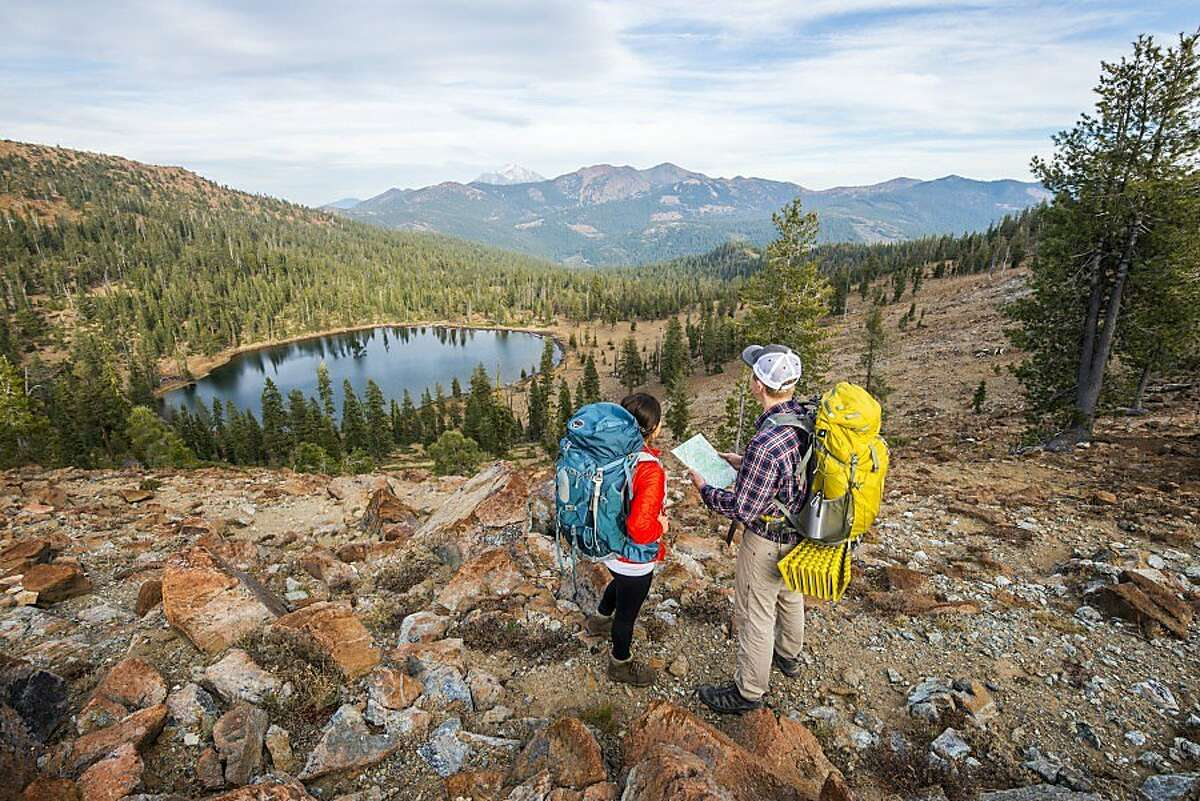 A pair of thru-hikers on the Pacific Crest Trail standing above Bull Lake in the Trinity Mountains.
