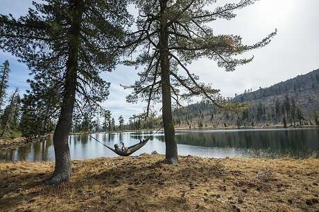 A man strums a guitar from a hammock next to Bull Lake, one of the alpine lakes on the Trinity Divide Project property. Photo: Rachid Dahnoun / Trust For Public Land