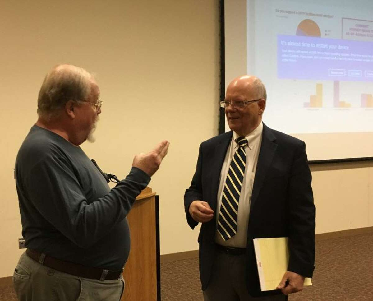 Cinco Ranch resident Philip Harang, left, talks with Fort Bend County Precinct 3 Commissioner Andy Meyers after a meeting held at the Cinco Ranch Branch Library to talk about a possible fall facilities bond referendum.