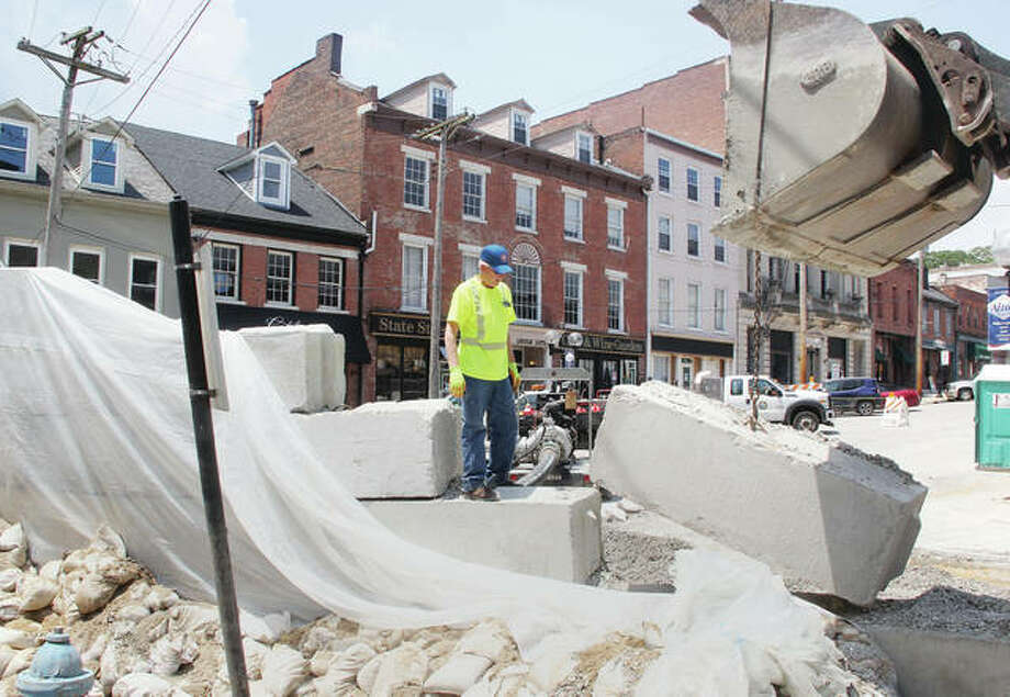 Alton Public Works employee Lloyd Roberts watches as a front-end loader removes a section of the flood wall at State and Broadway Wednesday afternoon. As the water recedes, workers have started the final process in removing the wall and cleaning and repairing the intersection, which should take about a week.
