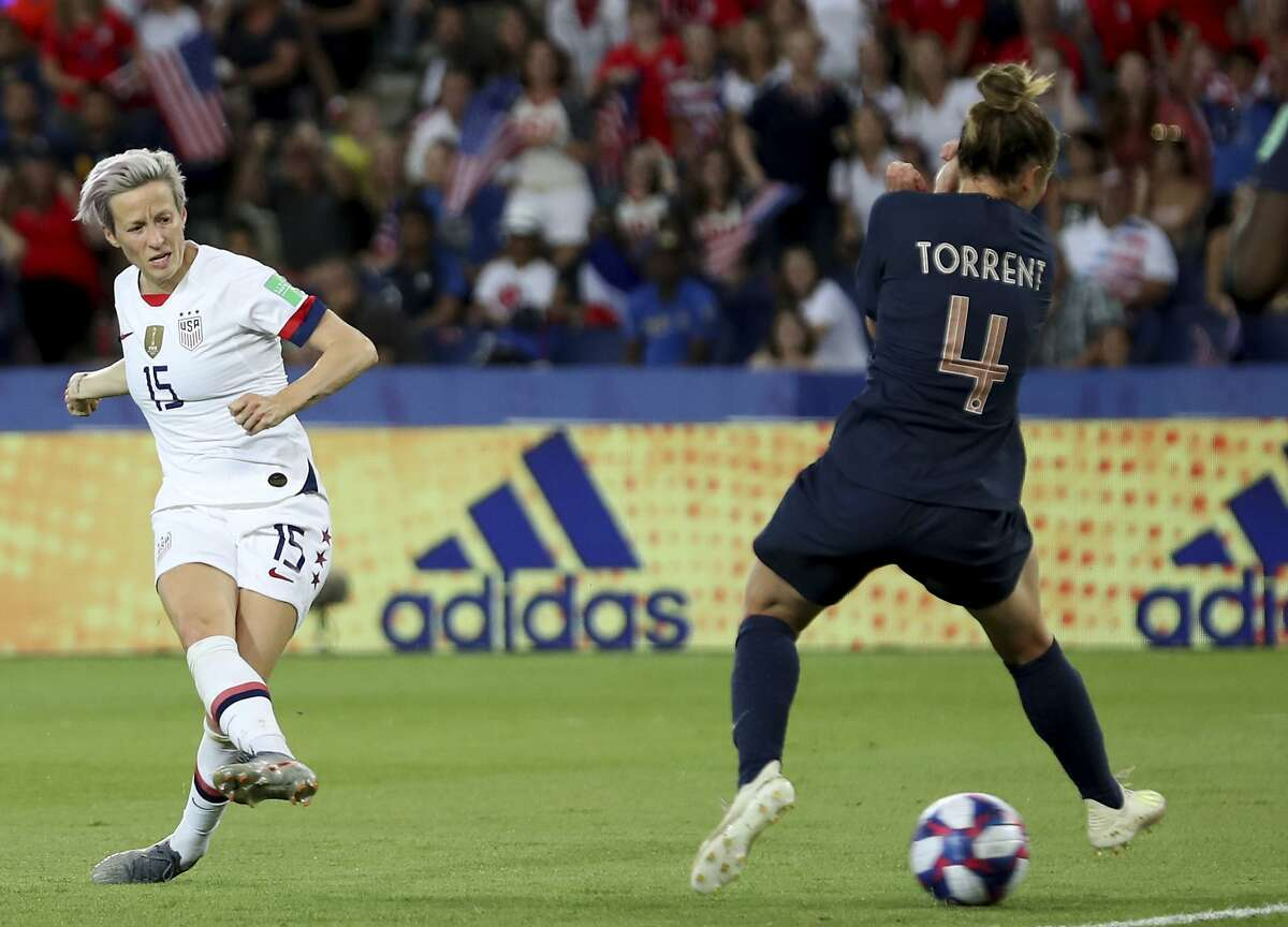 United States' Megan Rapinoe, left, on her way to scoring her side's second goal during the Women's World Cup quarterfinal soccer match between France and the United States at the Parc des Princes, in Paris, Friday, June 28, 2019. (AP Photo/Francisco Seco)