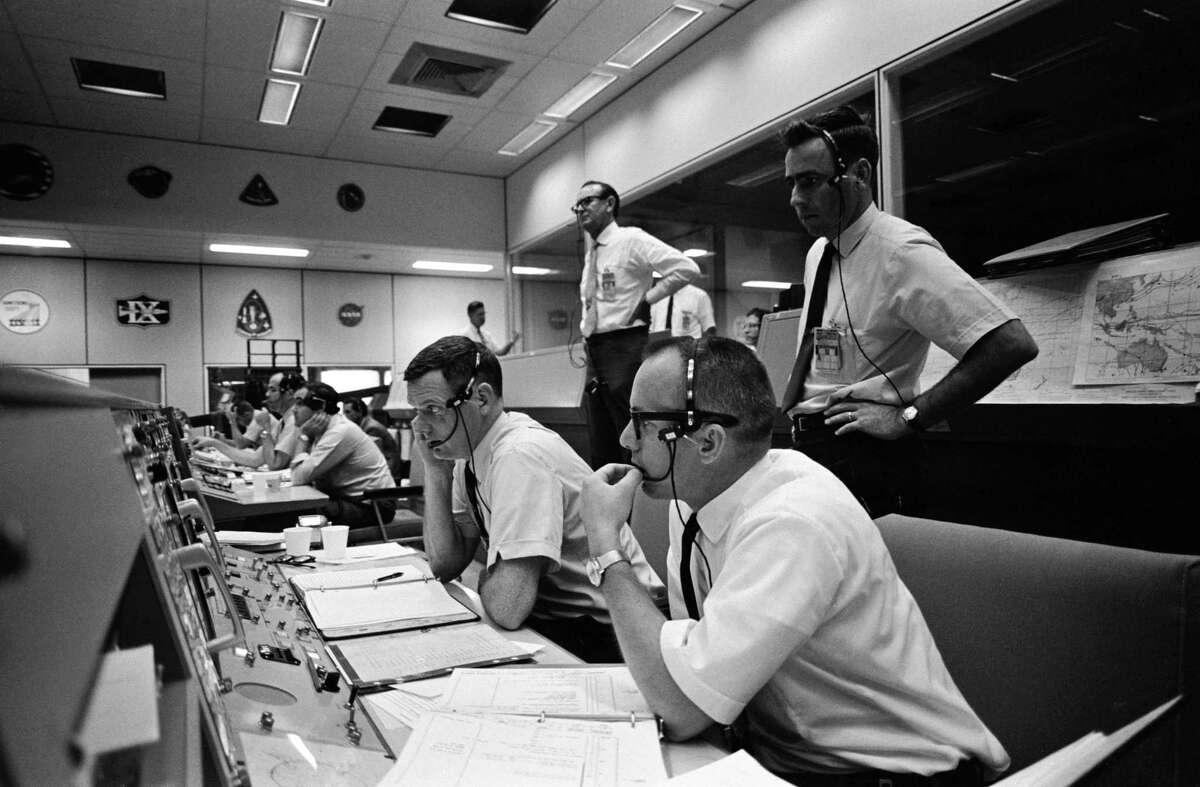 This photo from May 18, 1969 shows the flight director's console in the Mission Control Center on the first day of the Apollo 10 lunar orbit mission. Seated are, right to left, flight directors Gerald D. Griffin, Glynn S. Lunney and Milton L. Windler. Standing behind them in the center, background is Johnson Space Center Director of Flight Operations Christopher Kraft.