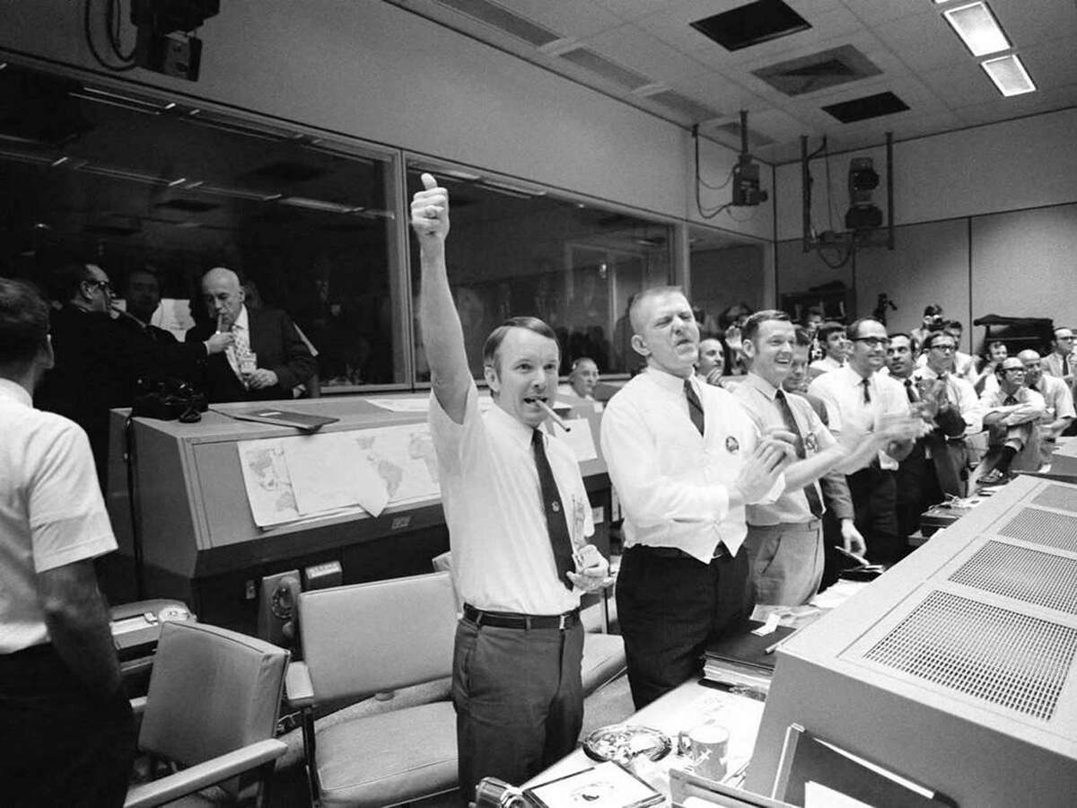 """In this April 17, 1970 photo, three of the four Apollo 13 flight directors, from left, Gerald D. Griffin, Gene Kranz and Glynn S. Lunney applaud the successful splashdown of the Command Module """"Odyssey."""" In upper left, Robert R. Gilruth, director of the Manned Spacecraft Center and Deputy Director Christopher Kraft light up cigars."""